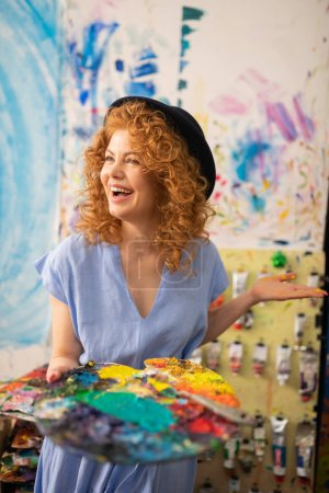 Photo for Artist feeling happy. Cheerful curly red-haired artist wearing black hat feeling happy while painting - Royalty Free Image