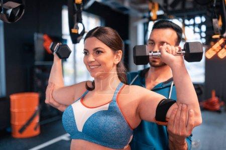 Photo pour Femme faisant des exercices. Entraîneur aidant femme positive faire des exercices pour les bras dans le centre de fitness - image libre de droit