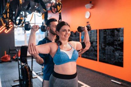 Photo pour Aide du formateur. Femme obèse faisant des exercices avec des haltères avec l'aide d'un entraîneur dans un centre de remise en forme - image libre de droit