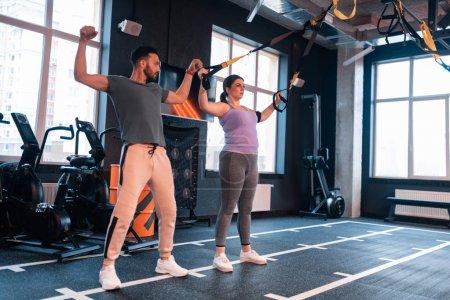 Photo pour Montrant des exercices de femme. Entraîneur sportif de fitness beau montrant des exercices de femme avec TRX - image libre de droit