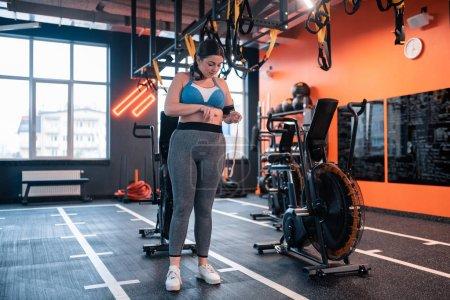 Photo pour Legging et haut. Femme dodue portant des leggings gris et la taille de mesure supérieure debout dans le centre de fitness - image libre de droit