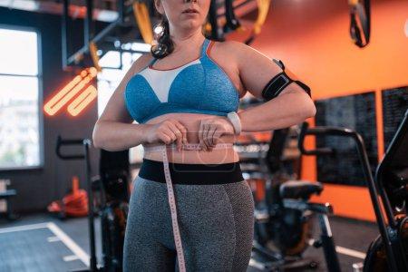 Photo pour Je porte un appareil de fitness. Femme dodue portant un haut court et un tracker de fitness mesurant la taille - image libre de droit