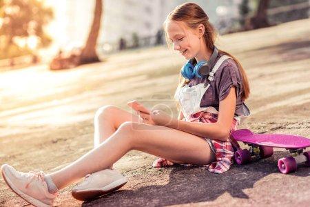 Photo pour Je vérifie le smartphone. Adolescente aux cheveux longs souriante divertie avec les médias sociaux tout en étant assise sur le sol nu - image libre de droit