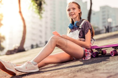 Photo pour Terre nue. Curieux jeune femme en tenue d'été ayant des écouteurs sur le cou tout en bavardant en messager sur un smartphone - image libre de droit