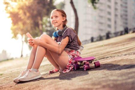 Photo pour Bavarder en messager. Petite dame positive avec les cheveux attachés assis seul dans la rue et se concentrant sur les médias sociaux - image libre de droit