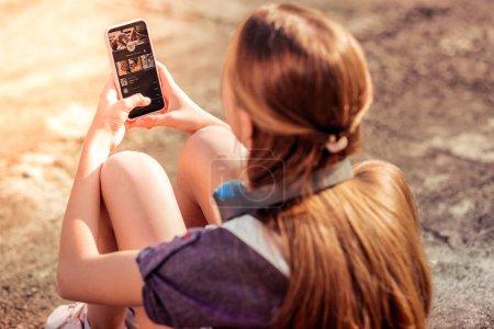 Photo pour Application smartphone. Adolescente aux cheveux longs portant un smartphone et choisissant la musique tout en ayant une humeur mélancolique - image libre de droit