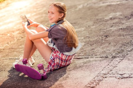 Photo pour Communiquer dans les médias sociaux. Joyeux fille aux cheveux longs rester sur le sol avec planche à roulettes à proximité tout en tenant téléphone mobile - image libre de droit