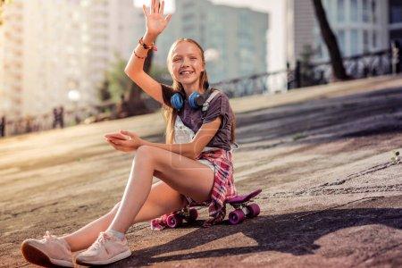 Photo pour Assis sur un skateboard. Rayonnant adolescente aux cheveux longs dans un t-shirt agitant la main tout en rencontrant des amis - image libre de droit