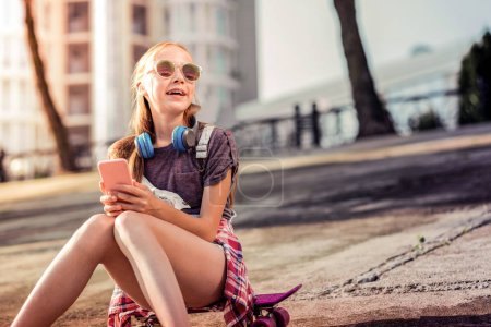 Photo pour Skateboard et smartphone. Jeune fille active dans des lunettes de soleil se refroidissant seul tout en étant assis sur une planche à roulettes rose - image libre de droit