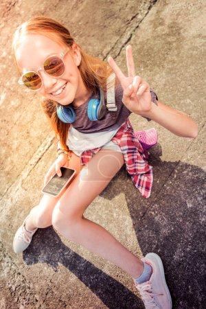 Photo pour Divertissant avec smartphone. Joyeux jeune fille en lunettes de soleil être de bonne humeur tout en restant à l'extérieur et en bavardant dans un smartphone - image libre de droit