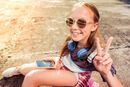 Photo pour Être de bonne humeur. Jolie petite fille avec un large sourire portant des lunettes de soleil sombres tout en montrant son humeur pendant la chaude journée d'été - image libre de droit