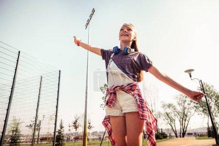 Photo pour Super vacances d'été. Adolescente indépendante aux cheveux longs avec des écouteurs sur le cou montrant son bonheur et son amusement - image libre de droit