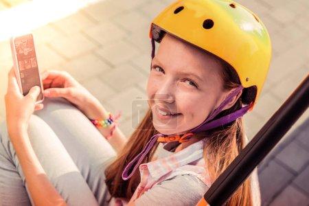 Photo pour Casque jaune. Rayonnant jeune fille aux cheveux longs passer des vacances d'été à l'extérieur et jouer sur un smartphone - image libre de droit