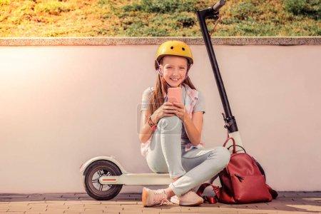 Photo pour Chatter sur un smartphone. Souriant belle adolescente en tenue légère assise sur scooter électronique avec sac à dos rouge à proximité - image libre de droit