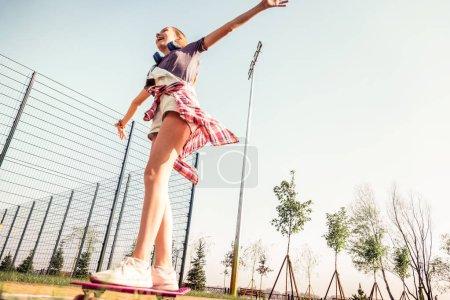 Photo pour J'étends les mains. Joyeux jeune fille en tenue d'été chevauchant à travers le parc vide sur une planche à roulettes tout en passant une journée chaude à l'extérieur - image libre de droit