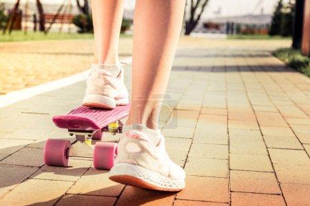 Photo pour Skateboard lumineux. Jeune fille dans des haut-parleurs confortables utilisant skateboard rose pour l'équitation tout en s'amusant à l'extérieur - image libre de droit