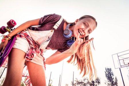 Photo pour Je porte des écouteurs. Rire jeune femme positive activement gesticuler et poser tout en restant à l'extérieur - image libre de droit