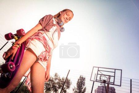Photo pour Saison estivale. Souriant belle fille profitant de vacances d'été chaudes tout en marchant avec skateboard rose - image libre de droit