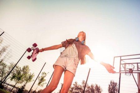Photo pour Aire de jeux vide. Rire fille brune profiter agréable journée d'été tout en ayant des vacances à l'école - image libre de droit