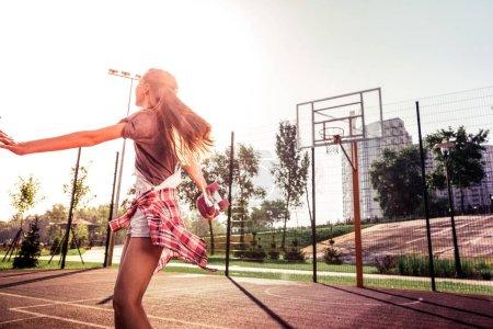 Photo pour Être sur une aire de jeux. Adolescente aux cheveux foncés se déplaçant activement tout en jouant le soir pendant la saison chaude d'été - image libre de droit
