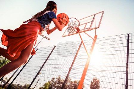 Photo pour Lancer la balle. Résolu fille forte avec les cheveux attachés passer soirée ensoleillée sur une aire de jeux tout en traitant avec ballon de basket - image libre de droit