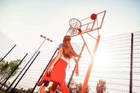 Photo pour Fille avec des compétences de basket. Femme active aux cheveux longs en tenue sportive confortable jouant au basket sur un terrain vide - image libre de droit
