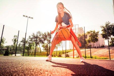 Photo pour Tenue confortable. Occupé fille attentive traitant avec balle de basket-ball lumineux tout en jouant sur une aire de jeux équipée - image libre de droit