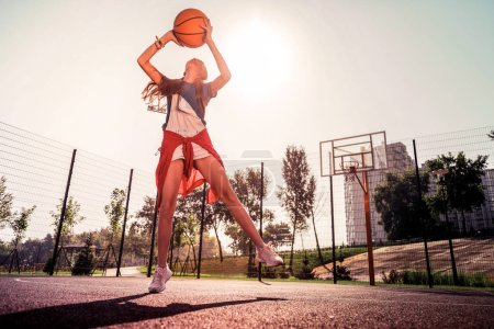 Photo pour Une fille expérimentée concentrée. Grande dame forte en tenue légère levant les mains avec balle en eux tout en jouant seul dans un parc vide - image libre de droit