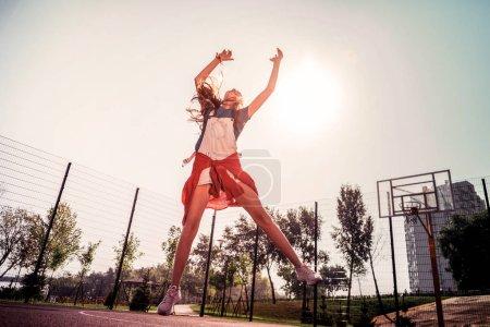Photo pour Jouer seul. Fille sportive excitée en vêtements d'été être impliqué dans le jeu actif tout en jouant sans amis - image libre de droit