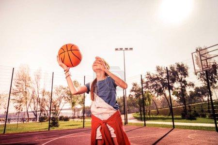 Photo pour Montrant des tours. Fille chevelue expérimentée jetant activement la balle orange pendant l'entraînement dans le parc - image libre de droit