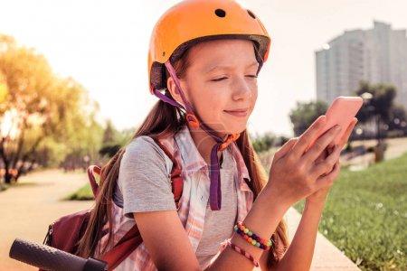 Photo pour Casque lumineux protecteur. Focalisé fille aux cheveux longs en casque orange bavarder sur un smartphone pendant le temps passé à l'extérieur - image libre de droit