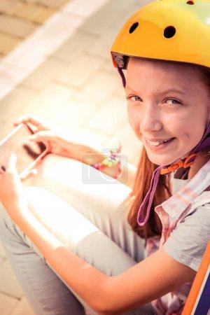 Photo pour Repos dehors. Joyeux jeune femme mignonne dans le casque jaune se divertissant avec l'application smartphone tout en étant assis dans les rayons du soleil - image libre de droit