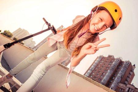 Photo pour Un geste de paix. attrayant jeune femme avec un large sourire étant d'humeur heureuse tout en chevauchant activement sur un scooter - image libre de droit