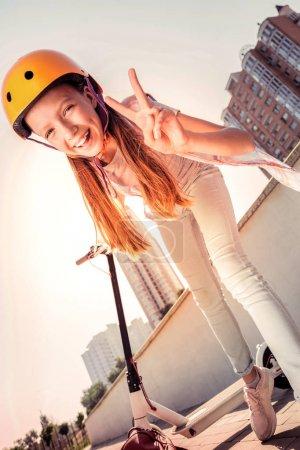 Photo pour Avoir un scooter personnel. Jeune femme positive en casque de protection jaune exposant son sentiment tout en circulant sur un scooter - image libre de droit