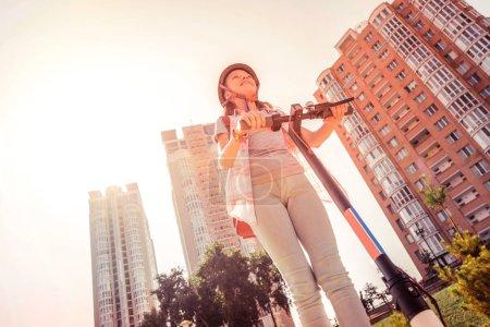 Photo pour Casque de protection jaune. Résolu dame active en munitions de protection à cheval sur un scooter innovant dans le salon - image libre de droit