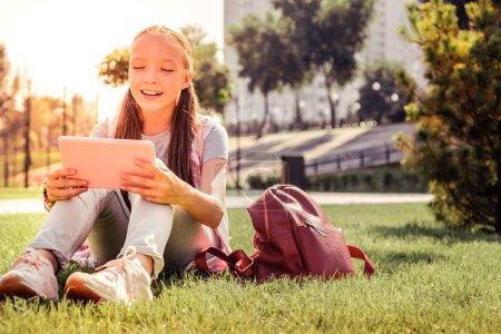 Photo pour Adolescente aux cheveux bruns. Jeune dame souriante se rafraîchissant sur une herbe verte et vérifier la tablette tout en surfant sur les médias sociaux - image libre de droit