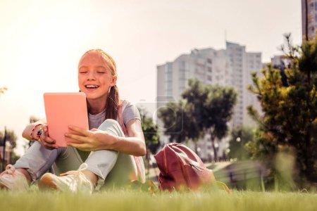 Photo pour Surfer sur les médias sociaux. rire belle fille être diverti avec contenu dans une tablette tout en se reposant dans la zone du parc - image libre de droit