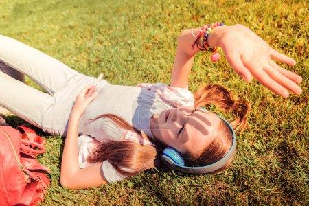 Photo pour Allongé sur une herbe. Brune fille maigre fermant la lumière du soleil avec sa paume tout en refroidissant sur une pelouse fraîche - image libre de droit