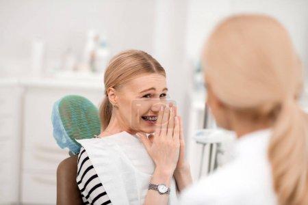 Photo pour Même les dents. Jeune dentiste patiente levant les mains sur son visage étant heureuse d'avoir ses nouveaux appareils . - image libre de droit