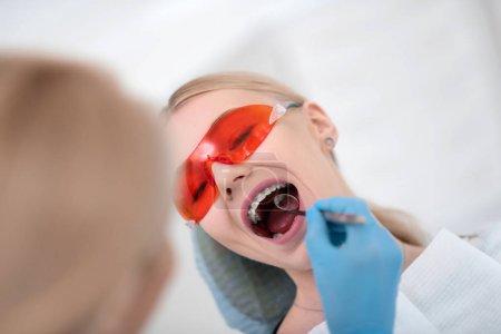 Photo pour J'examine les dents. Dentistes joyeux patient portant des lunettes de protection rouges ouvrant sa bouche lors de son inspection médicale . - image libre de droit