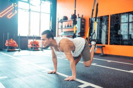 Photo pour Dans la salle de gym. Homme en forme sérieux faisant un exercice physique spécial tout en travaillant dans la salle de gym - image libre de droit