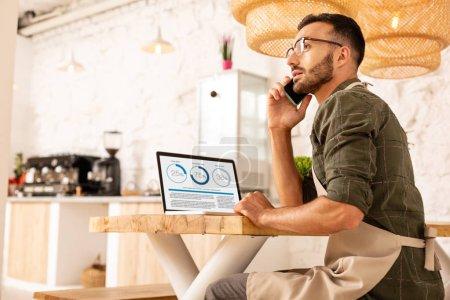 Photo pour Appel à l'investisseur. Homme d'affaires barbu surchargé appelant l'investisseur tout en s'asseyant dans le café - image libre de droit
