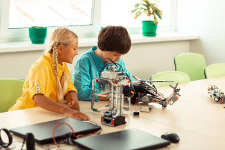 Photo for Working in team. Two enthusiastic classmates sitting at the desk and building models using construction set at science lesson. - Royalty Free Image