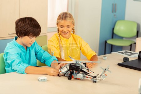 Photo for Overseeing work. Cheerful smiling girl looking at her classmate building a helicopter of construction set during science lesson. - Royalty Free Image