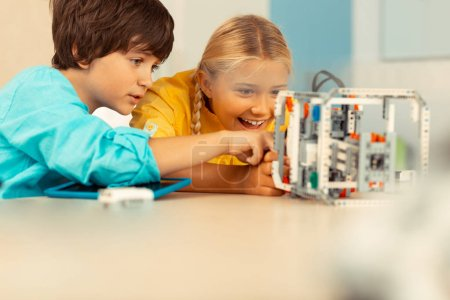 Photo for Impressed by learning. Two excited schoolchildren looking closely and playing with the robot at their science class. - Royalty Free Image