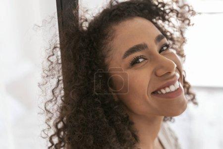 Photo pour Bonne humeur. Joyeux brunette fille garder le sourire sur son visage tout en regardant la caméra - image libre de droit