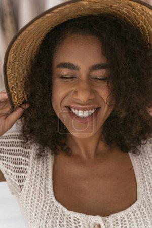 Photo pour Amour d'été. Joyeuse fille gardant les yeux fermés tout en essayant nouveau chapeau - image libre de droit