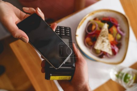 Photo for Close up of female hand holding mobile phone over terminal for contactless payment - Royalty Free Image