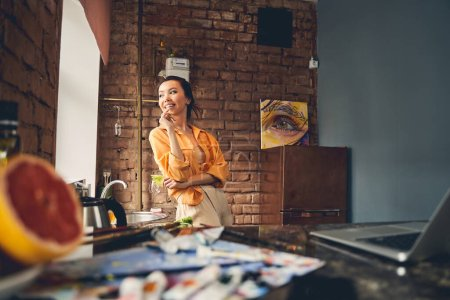 Photo for Beautiful young woman eating fresh lettuce and smiling while standing by kitchen counter - Royalty Free Image