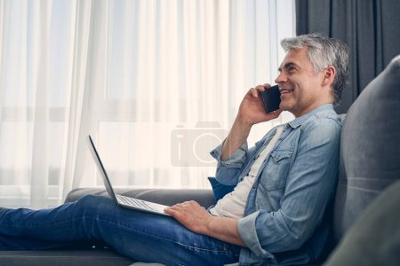 Photo for Attractive grey haired male enjoying time at home while working on his laptop and communicating on smartphone - Royalty Free Image